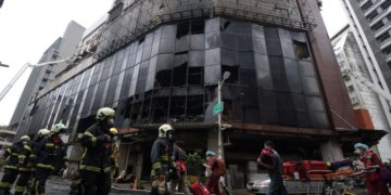 Firefighters and medical workers walk past a damaged residential building following a fire in Kaohsiung [Woo Swee Kay/Reuters] Published On